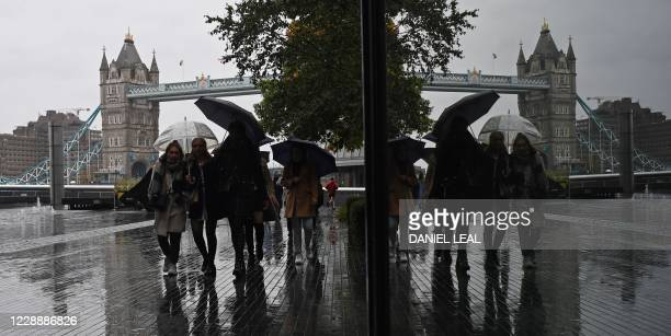 People sheltering from the rain under umbrellas are reflected in a window as they walk beside the River Thames near to Tower Bridge in central London...