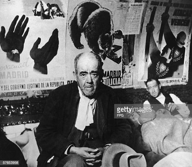 People sheltering in the Madrid Metro during the Spanish Civil War circa 1937 Republican posters line the wall behind them one depicting a bear...