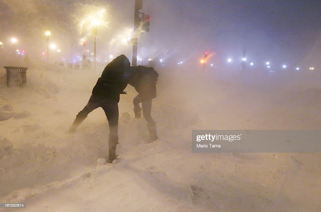 People shield themselves from the blowing snow as a blizzard arrives in the Back Bay neighborhood on February 8, 2013 in Boston, Massachusetts. Massachusetts and other states from New York to Maine are hunkered down for the major blizzard with possible record amounts of snowfall in some areas.