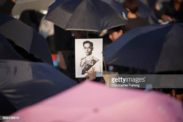 People shield themselves from the heat as hundreds of thousands of people dressed in black attend the funeral of the late Thai King Bhumibol...