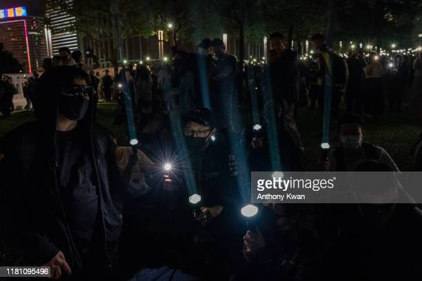 people shine their flashlights during a remembrance prayer in memory of an university student Alex Chow who succumbed to head injuries sustained...