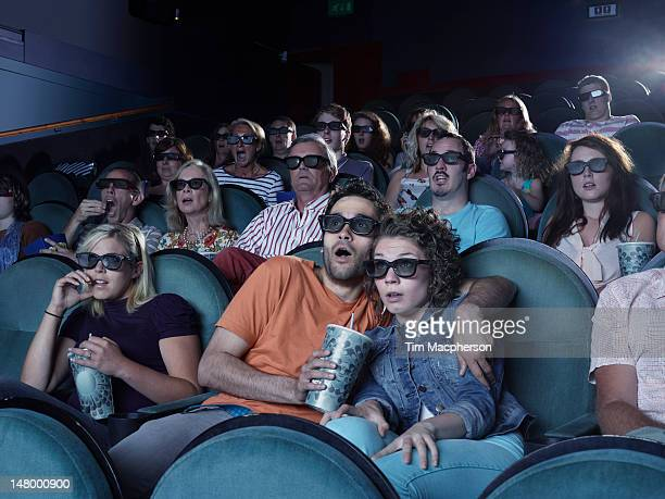 People shocked watching a movie at a theater