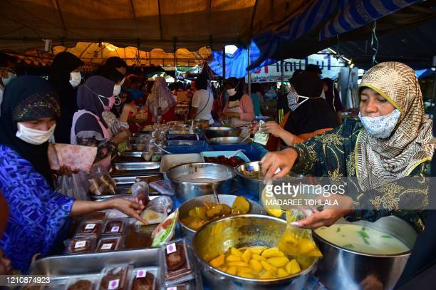 People shop at a food market on the first day of the Muslim holy month of Ramadan in Thailand's southern province of Narathiwat on April 24 2020