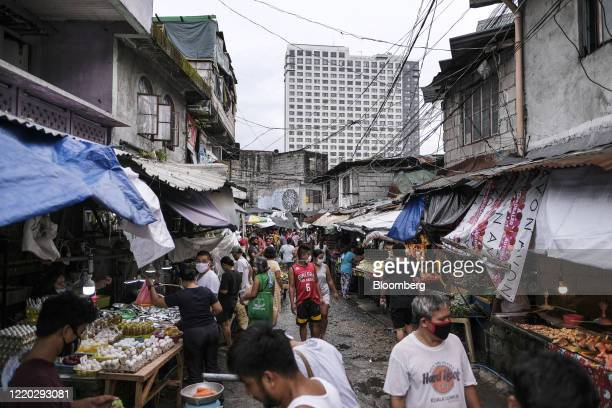 People shop at a makeshift market in the San Roque neighborhood as a commercial high-rise building stands in the background in Quezon City, Metro...