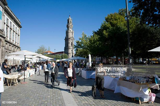 People shop at a street market selling tourist trinkets in a square near the Clerigos Church the Clerigos Tower can be seen in the background