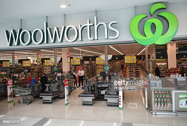 People shop at a Woolworths store in Sydney on August 25 2016 Australian supermarket giant Woolworths on August 25 reported a large annual net loss...