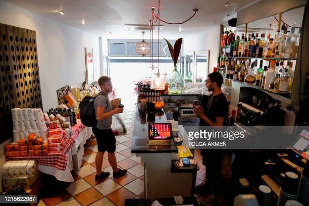 People shop at Ciullosteria, an Italian restaurant turned into a 'deli' specialising in Italian products, in Balham, south London on May 27 as...