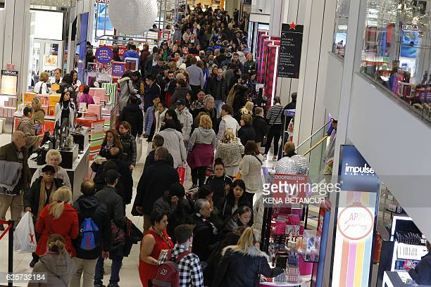 People shop at Macy's department store during the Black Friday sales on November 25 2016 in New York Shares of leading retailers rose early Friday...