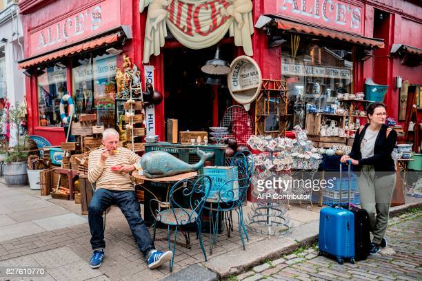 People shop at Portobello Road Market in the Notting Hill district of west London on August 8 2017 Last week The Bank of England cut its UK growth...
