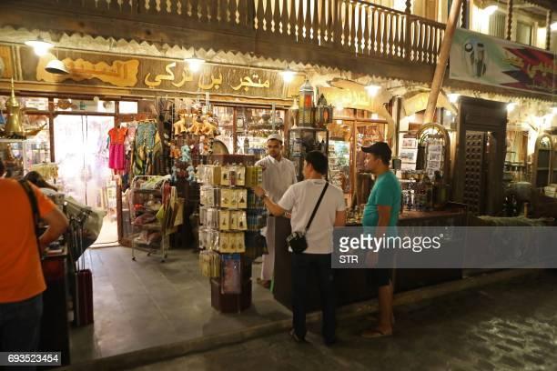 People shop at the popular Souq Waqif market in the Qatari capital Doha on June 7 2017 Saudi Arabia Egypt the UAE and Bahrain announced on June 5...