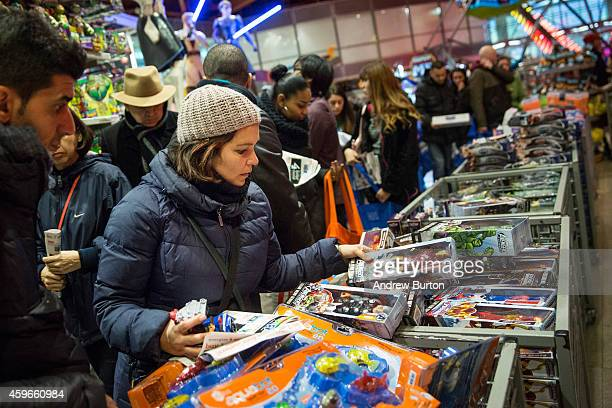 People shop at the Toys R Us in Times Square on November 27, 2014 in New York, United States. Black Friday sales, which now begin on the Thursday of...