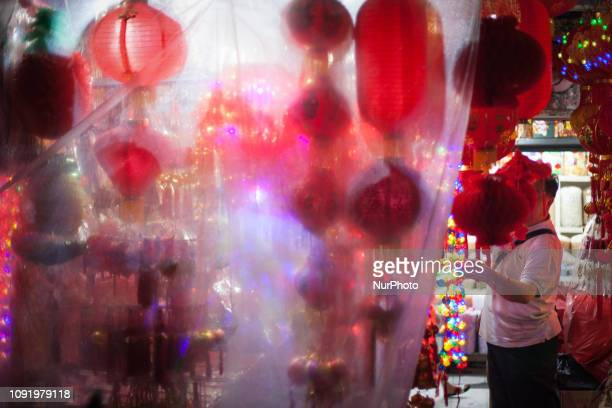 People shop for Chinese New Year decorations at a shop selling Chinese New Year decorations at night in the Chinatown in Jakarta Indonesia on January...
