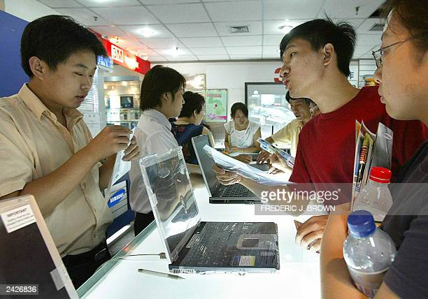 People shop for laptop computers at a techmall in Beijing 23 August 2003 The SobigF worm computer virus may have attacked more than 30 percent of...