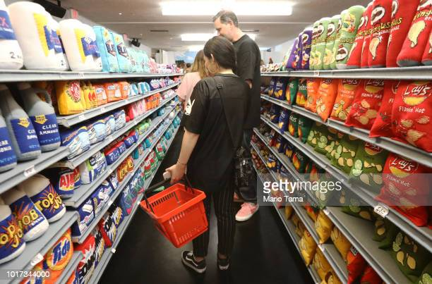 Artist Lucy Sparrow poses in an aisle of replica groceries made of felt at her 'Sparrow Mart' installation on August 15 2018 in Los Angeles...