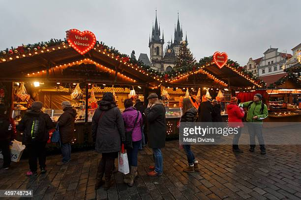 People shop in a Christmas market at the Old Town Square on November 30 2014 in Prague Czech Republic Christmas markets traditionally selling mulled...