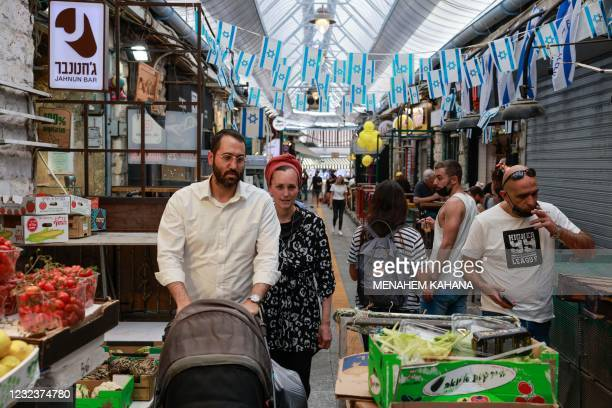 People shop in a market in Jerusalem, on April 18 after Israeli authorities announced that face masks for COVID-19 prevention were no longer required...
