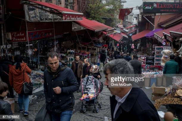 People shop in a market street on November 22 2017 in Istanbul Turkey The Turkish Lira plunged to a record low of 3978 against the dollar on Tuesday...