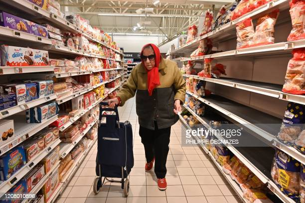 People shop in a supermarket open one hour only for the elderly and vulnerable on March 23 2020 in SaintEtienne central France on the seventh day of...
