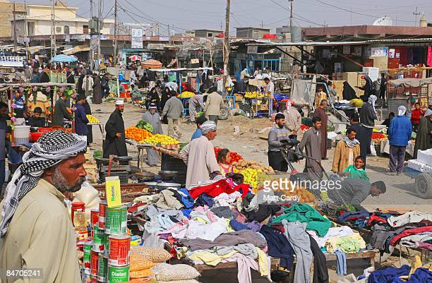 People shop in Al Qurnah market as Iraqi soldiers and British soldiers from 1st Battalion The Yorkshire Regiment patrol close to the claimed biblical...