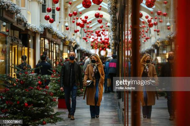 People shop in Burlington Arcade in Mayfair on December 12, 2020 in London, England.