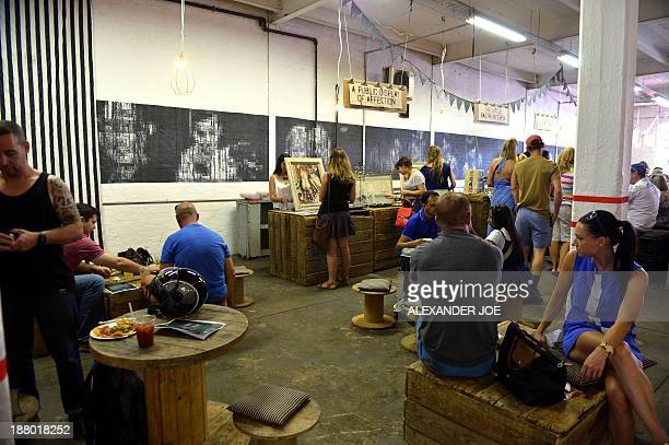 People shop on market day in Maboneng the hippest neighborhood in downtown Johannesburg on November 10 2013 A precinct of cafes boutiques and loft...