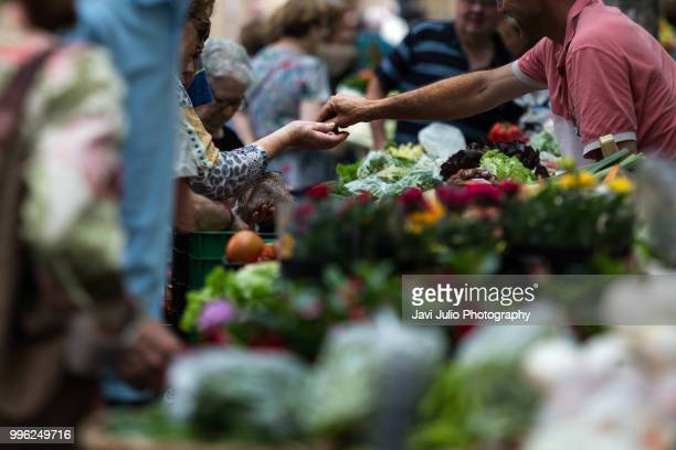 People shoping at a traditional outdoor fruit and vegetable market in San Sebastian, Spain