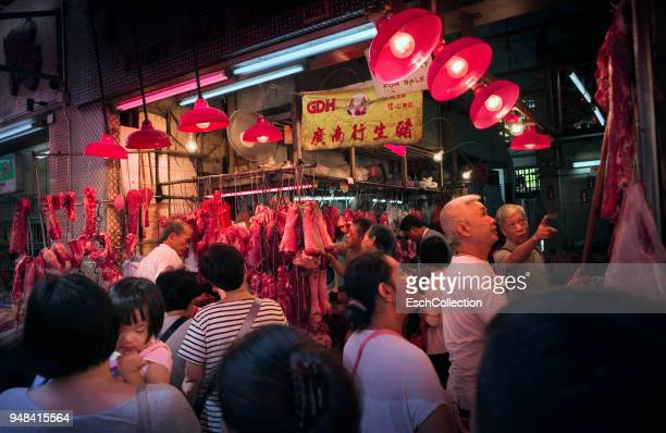 People shopping at a traditional butcher in Hong Kong at dawn