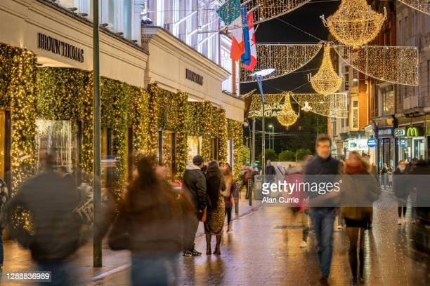 people shopping at christmas in dublin city centre at grafton street outside brown thomas - brown thomas christmas stock pictures, royalty-free photos & images