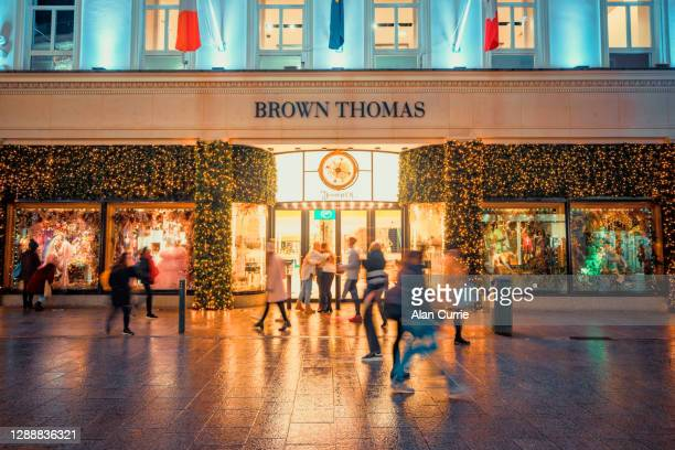 people shopping at christmas in dublin city centre outside brown thomas, grafton street - brown thomas christmas stock pictures, royalty-free photos & images