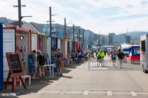 people shopping at the harbourside market in wellington, new zealand - wellington new zealand stock photos and pictures