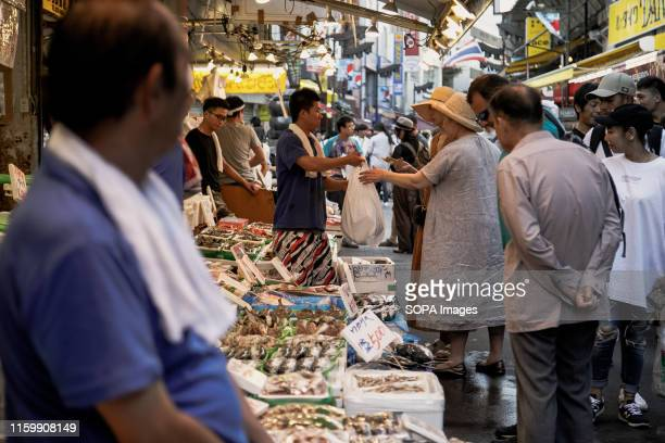 People shopping for fresh fish at the Ameya Yokocho market in Tokyo There are about 500 stores along the narrow lane which is visited by tens of...