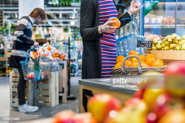 People shopping fruits while standing in supermarket