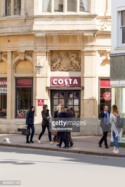 People shopping in Cheltenham town centre, passing the retail coffee outlet - Costa Coffee