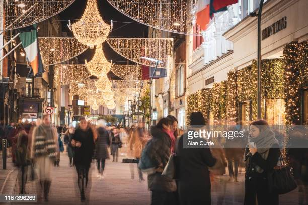 people shopping on grafton street outside brown thomas, dublin with christmas lights - brown thomas christmas stock pictures, royalty-free photos & images