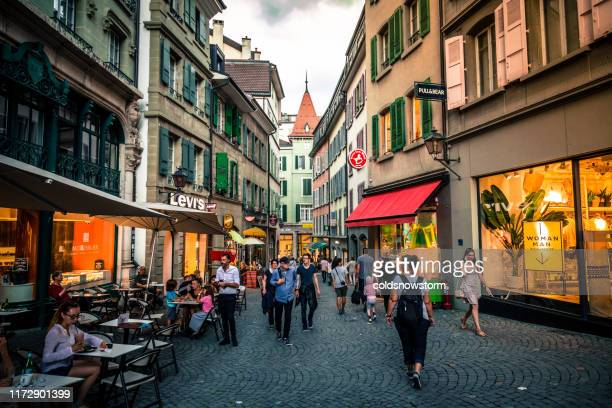 people shopping outdoors in old town architecture of lausanne, switzerland - lausanne stock pictures, royalty-free photos & images