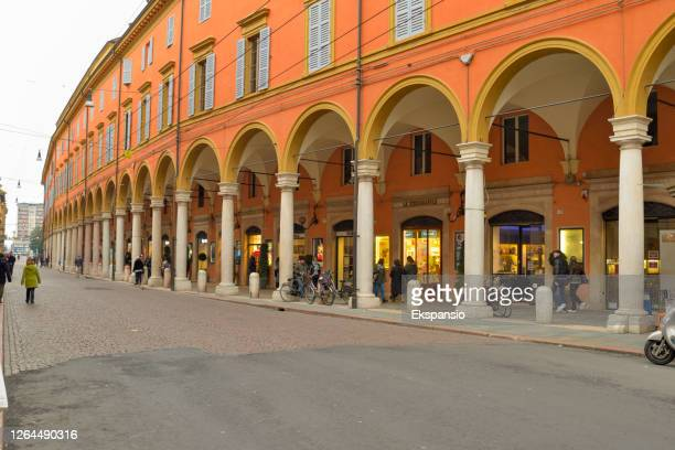 people shopping under colonnade in modena italy - modena stock pictures, royalty-free photos & images