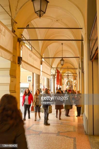menschen einkaufen unter kolonnade in modena italien - modena stock-fotos und bilder