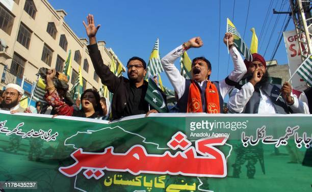 People shout antiIndia slogans as they hold a banner during a demonstration to mark Black Day in Muzaffarabad the capital of Pakistanadministered...