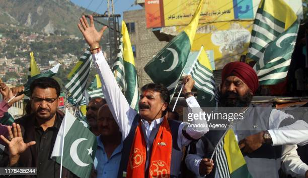 People shout antiIndia slogans as they hold Pakistani flags during a demonstration to mark Black Day in Muzaffarabad the capital of...