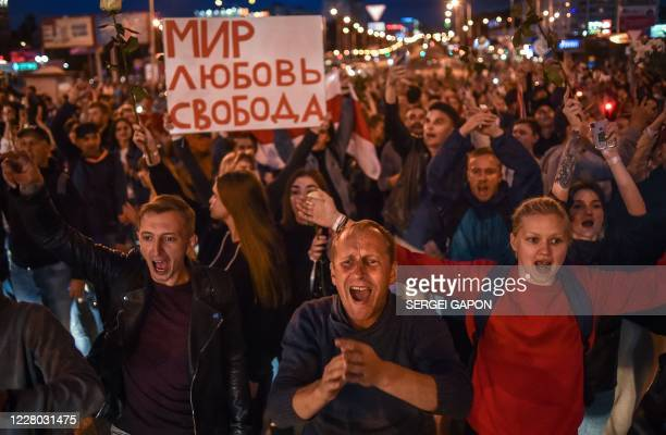 """People shout as they hold a poster reding """"Peace, Love, Freedom"""" during a protest rally against police violence during recent rallies of opposition..."""