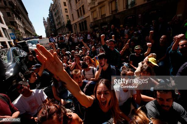 People shout in front of the headquarters of Catalonia's regional foreign affairs ministry in Barcelona on September 20 2017 Thousands took to the...