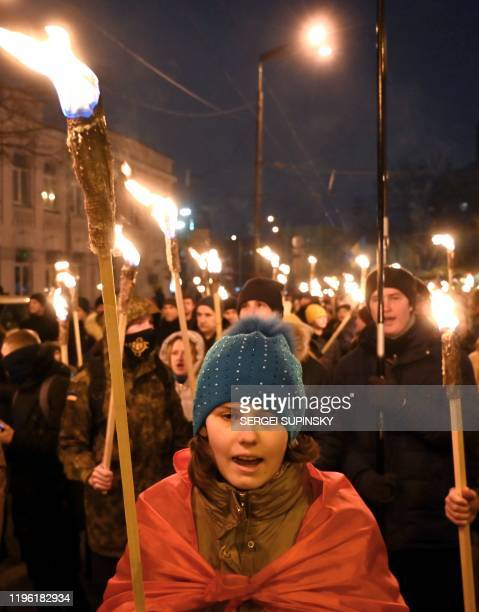 People shout slogans and carry torches during a march in Kiev on January 25 to mark the 102nd anniversary of a battle near the small Ukrainian city...
