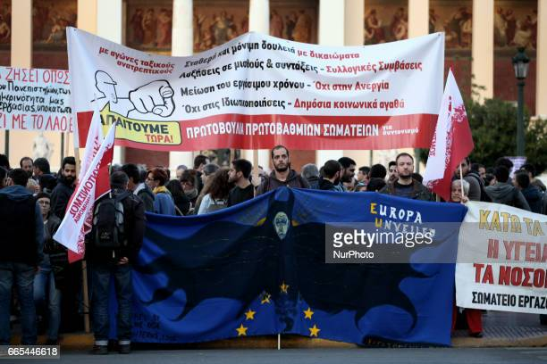 People shout slogans and hold banners during a protest against new austerity measures that impose further cuts in pension and funds in Athens Greece...