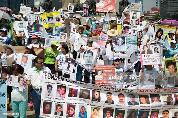 People shout slogans and hold photographs of their disappeared relatives during a march on Mother's Day on May 08 2016 in Mexico City Mexico Mothers...