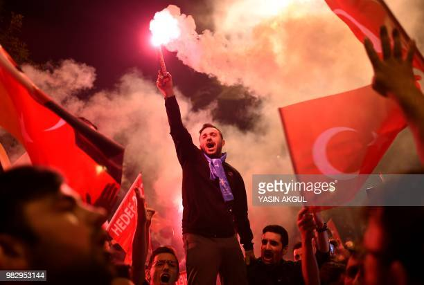 TOPSHOT People shout slogans and let off flares outside the Justice and Development Party headquarters Istanbul on June 24 after counting of votes in...