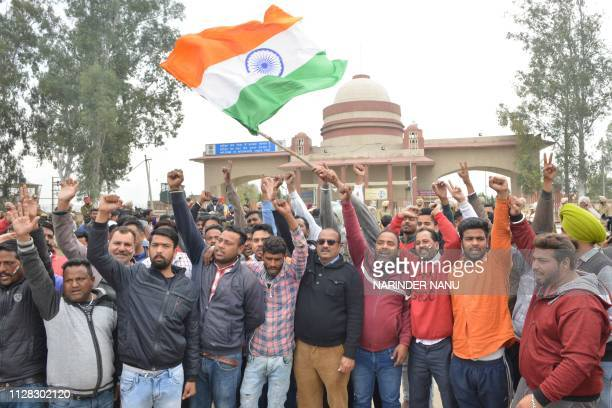 People shout slogans and wave the national flag near the IndiaPakistan border in Wagah on March 1 as they wait for the return of an Indian Air Force...