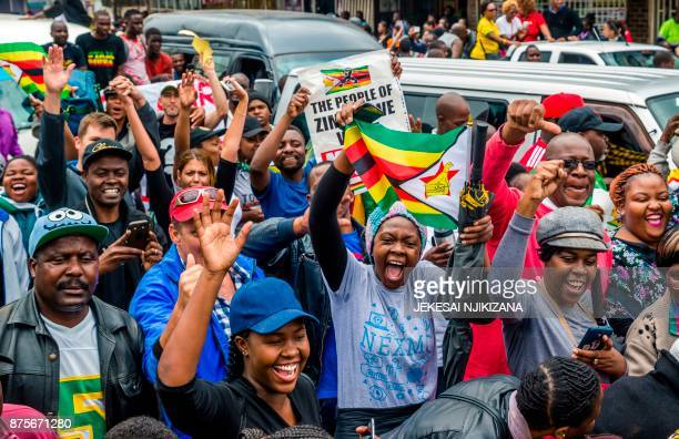People shout slogans and wave Zimbabwean national flags during a demonstration demanding the resignation of Zimbabwe's president on November 18 2017...