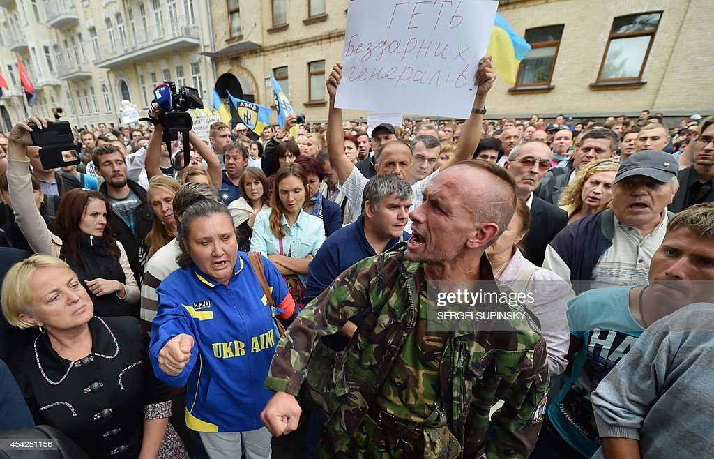 People shout slogans as they hold a placard 'Down with incompetent generals!' during a rally in front of Ukrainian President Petro Poroshenko's office in Kiev on August 27, 2014. Protesters demand help for the volunteer battalions of Donbass, Mirotvorets, Kherson and Dnipro-1 surrounded by pro-Russian militants for the fifth day in the small city of Izvaryne, suburb of the eastern Ukrainian city of Donetsk.