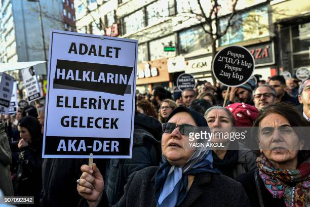 People shout slogans as they hold placards reading 'People will get justice' in front of the offices of Armenian weekly newspaper 'Agos' during a...