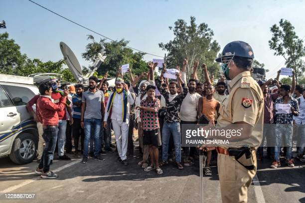 People shout slogans facing the police as they protest against the alleged gang-rape and murder of a 19-year-old woman in Bool Garhi of Hathras...